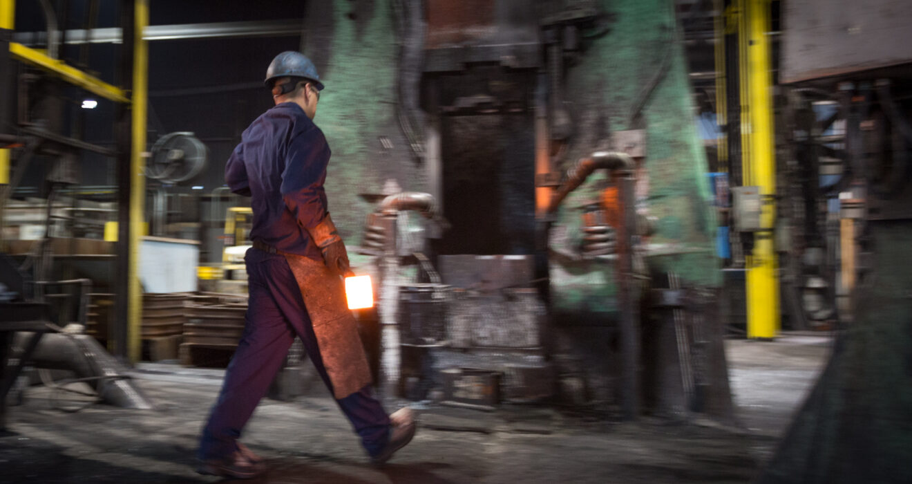 worker carrying hot billet towards hammer
