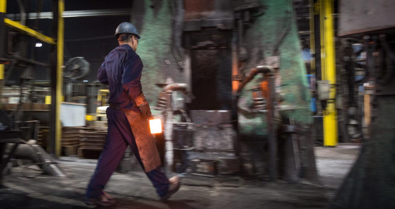 worker carrying hot billet towards hammer