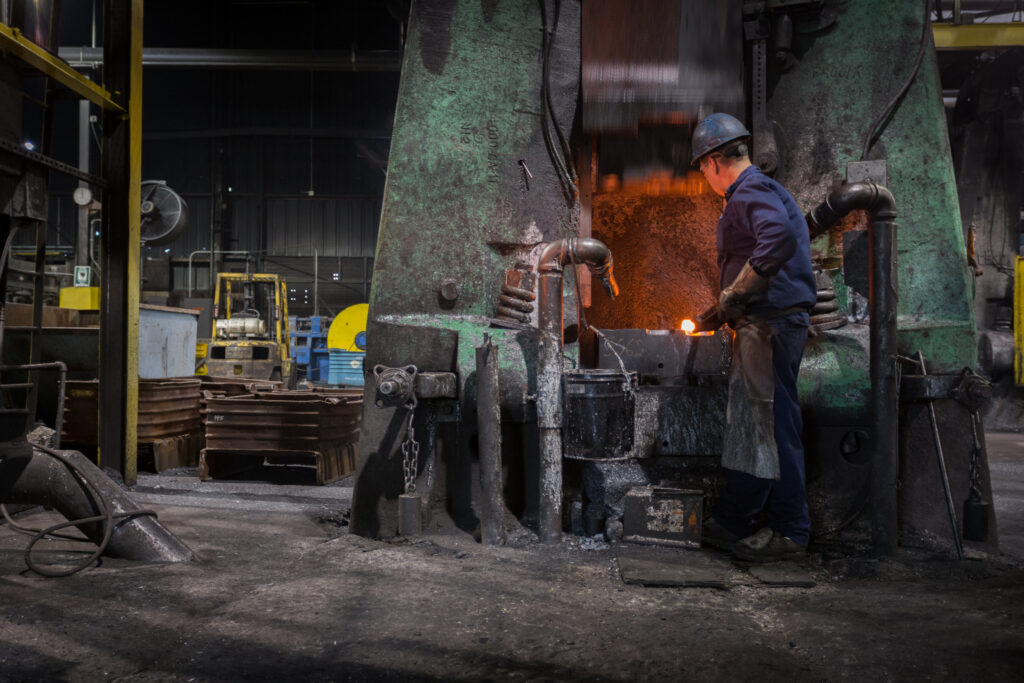 Worker at closed-die forging hammer placing hot billet