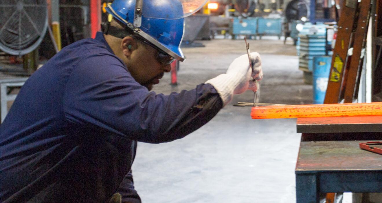 worker taking measurements of hot billet