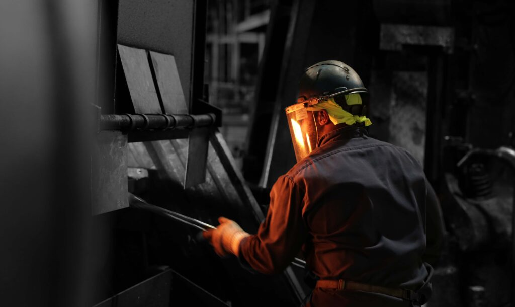 Black and white photo with man working near furnace