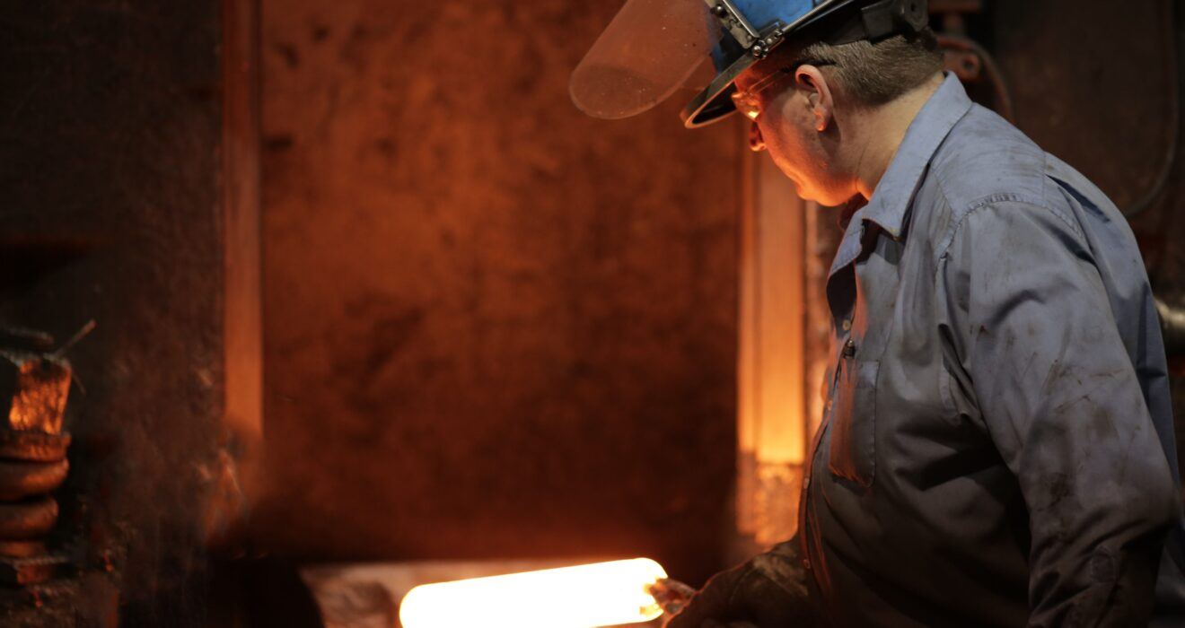 worker inspecting red hot billet of steel in hammer area