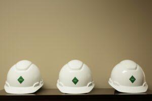 white safety hard hats on shelf